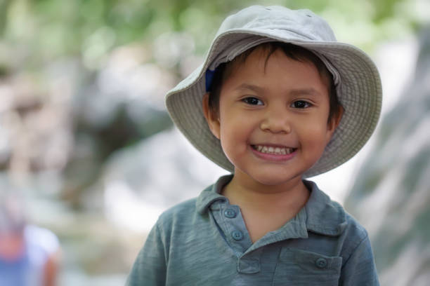 Young hispanic boy wearing a fishing hat that is smiling and looks happy in a natural outdoor setting. stock photo