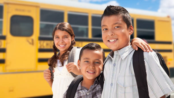 Young Hispanic Boys and Girl Walking Near School Bus Young Hispanic Boys and Girl Walking Near School Bus. latin american and hispanic ethnicity stock pictures, royalty-free photos & images