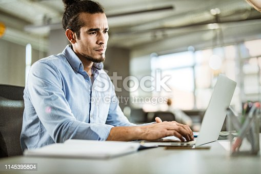 Hispanic programmer coding a language on laptop in the office.
