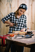 Young Hispanic carpenter woman working with hammer and nail on wood planks at home workshop