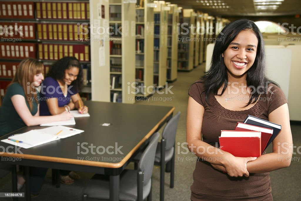 Young Hispanic College Student Holding Books in the University Library royalty-free stock photo
