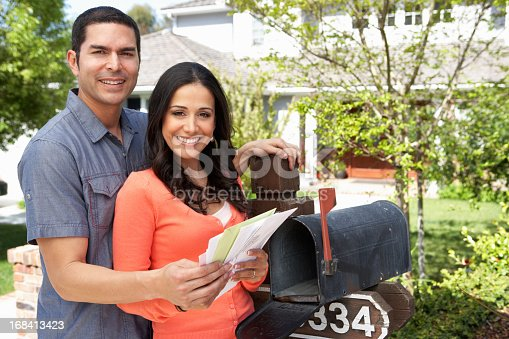 istock Young Hispanic couple checking the mailbox at their home 168413423