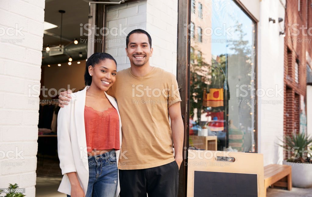 Young Hispanic couple smiling to camera outside their shop stock photo