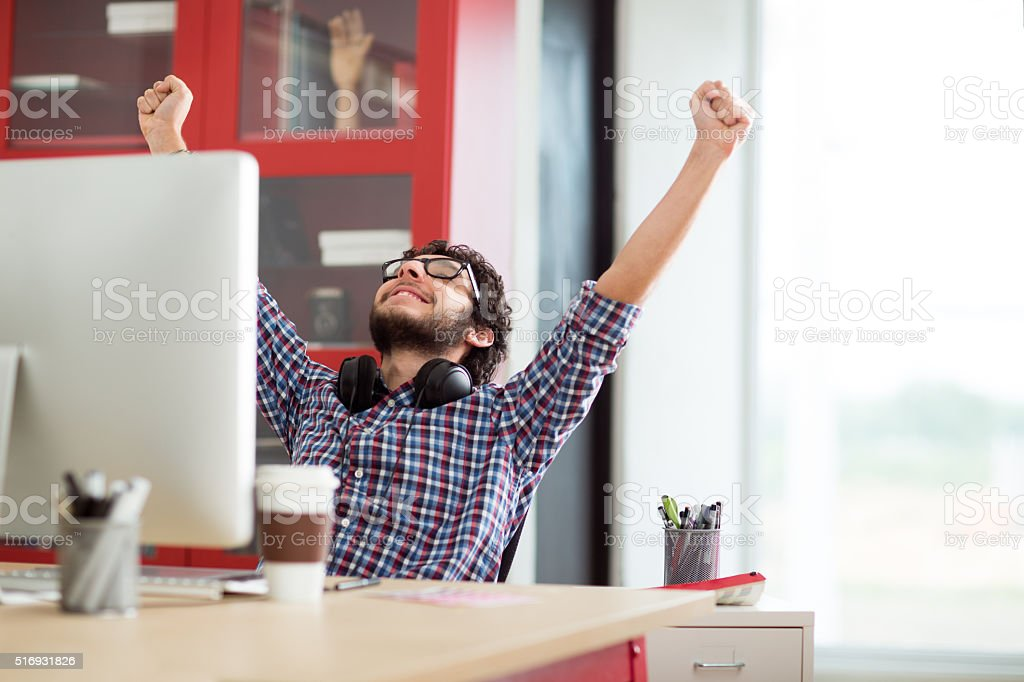 Young hispanic designer celebrating stock photo
