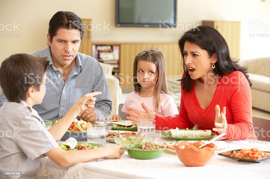 Young Hispanic Family Arguing While Eating Meal At Home stock photo
