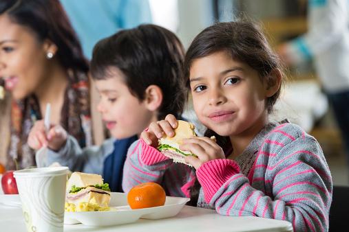Young Hispanic family eating meal at neighborhood soup kitchen