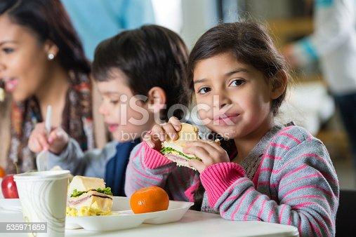 istock Young Hispanic family eating meal at neighborhood soup kitchen 535971659