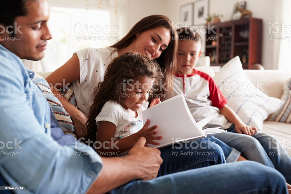 Young Hispanic family of four sitting on the sofa reading book together in their living room royalty-free stock photo