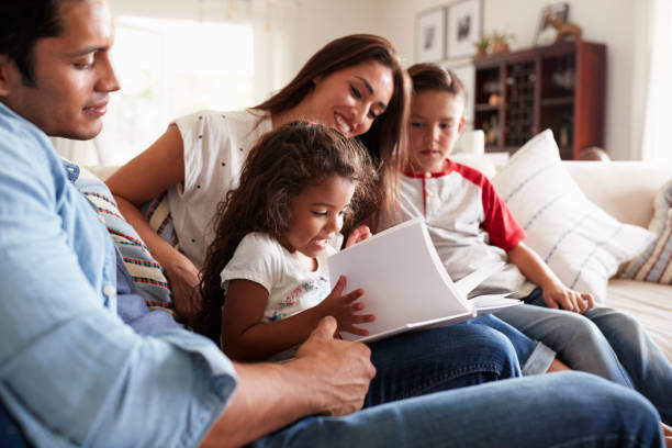 Young Hispanic family of four sitting on the sofa reading book together in their living room Young Hispanic family of four sitting on the sofa reading book together in their living room four people stock pictures, royalty-free photos & images