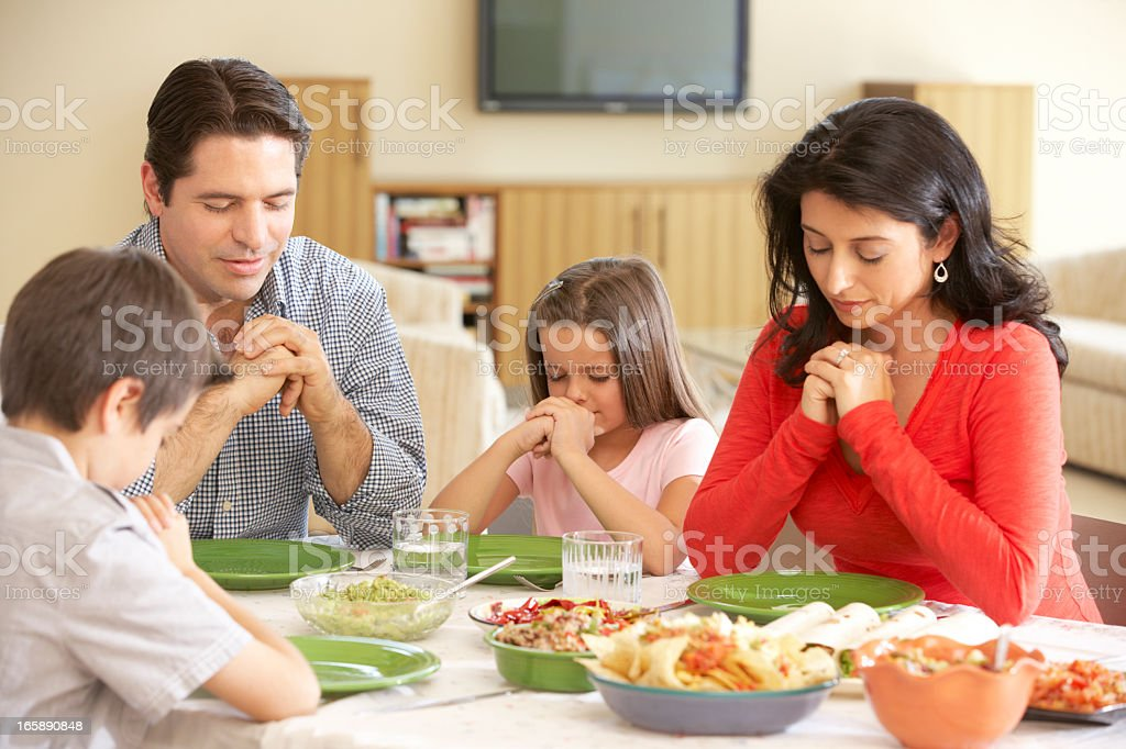 Young Hispanic Family Saying Prayers Before Meal At Home royalty-free stock photo