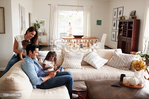 istock Young Hispanic family sitting on sofa reading a book together in their living room 1094435244