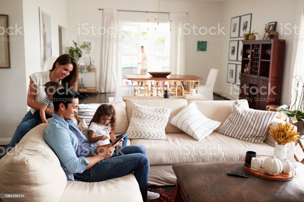 Young Hispanic family sitting on sofa reading a book together in their living room stock photo