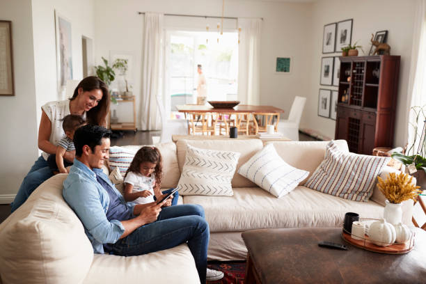 young hispanic family sitting on sofa reading a book together in their living room - generazioni foto e immagini stock