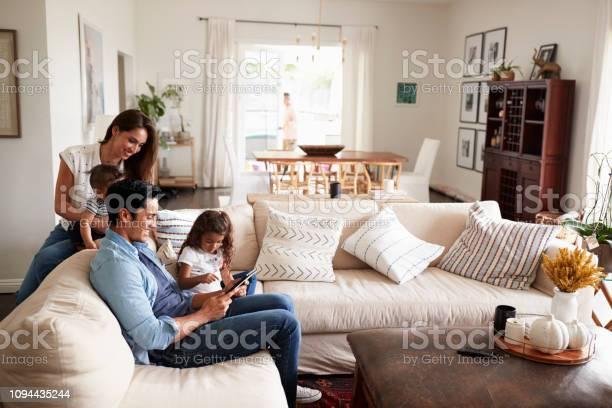 Jonge Spaanse Familie Zittend Op De Bank Samen Lezen Van Een Boek In Hun Woonkamer Stockfoto en meer beelden van 20-29 jaar
