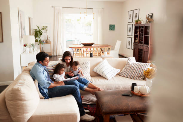 Young Hispanic family sitting on sofa reading a book together in the living room, seen from doorway Young Hispanic family sitting on sofa reading a book together in the living room, seen from doorway comfortable stock pictures, royalty-free photos & images