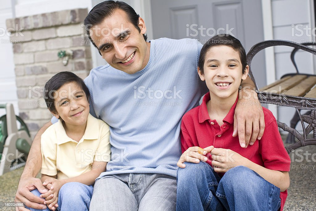 young hispanic father sitting outside with his boys royalty-free stock photo