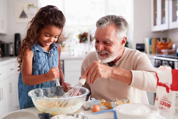 young-hispanischen mädchen und ihr opa schlagen kuchenteig gemeinsam am küchentisch, nahaufnahme - enkelin stock-fotos und bilder