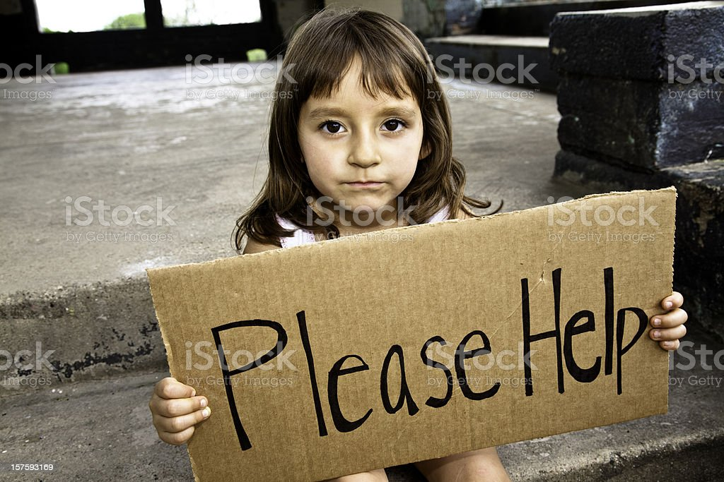 Young Hispanic Girl Holding a Please Help Sign stock photo