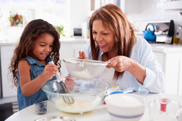 Young Hispanic girl making cake in the kitchen with her grandma, close up Young Hispanic girl making cake in the kitchen with her grandma, close up granddaughter stock pictures, royalty-free photos & images