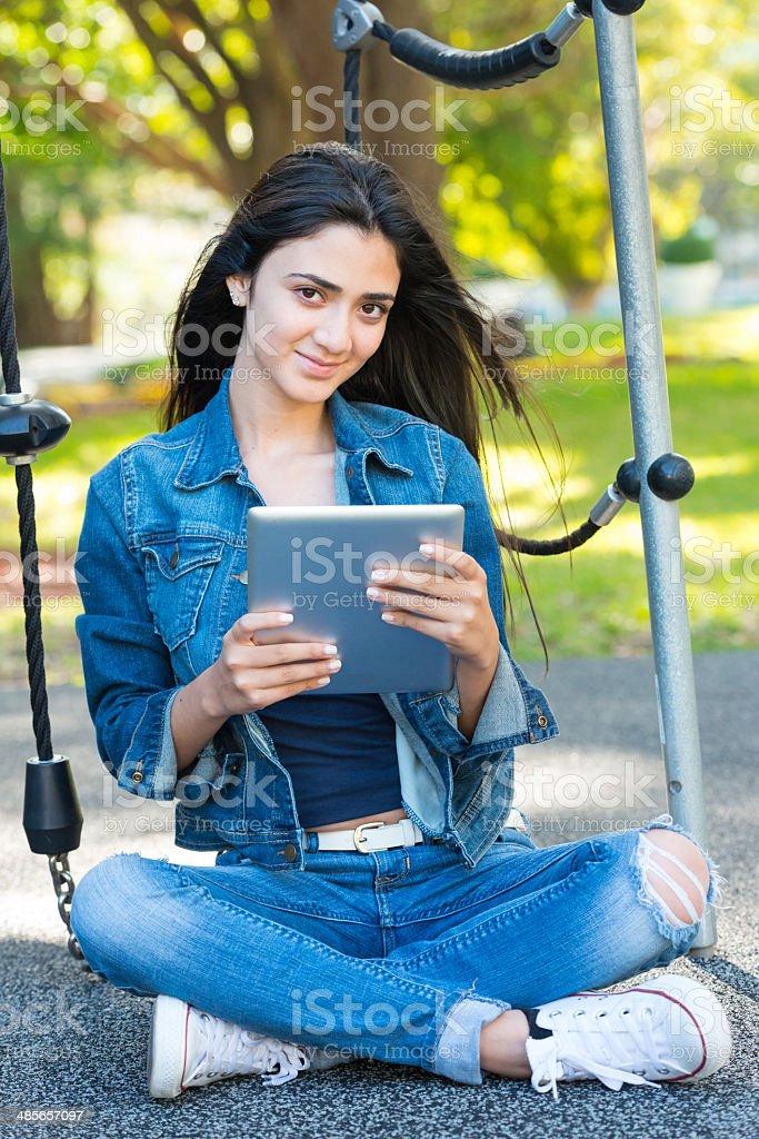 Young hispanic girl using her electronic tablet royalty-free stock photo