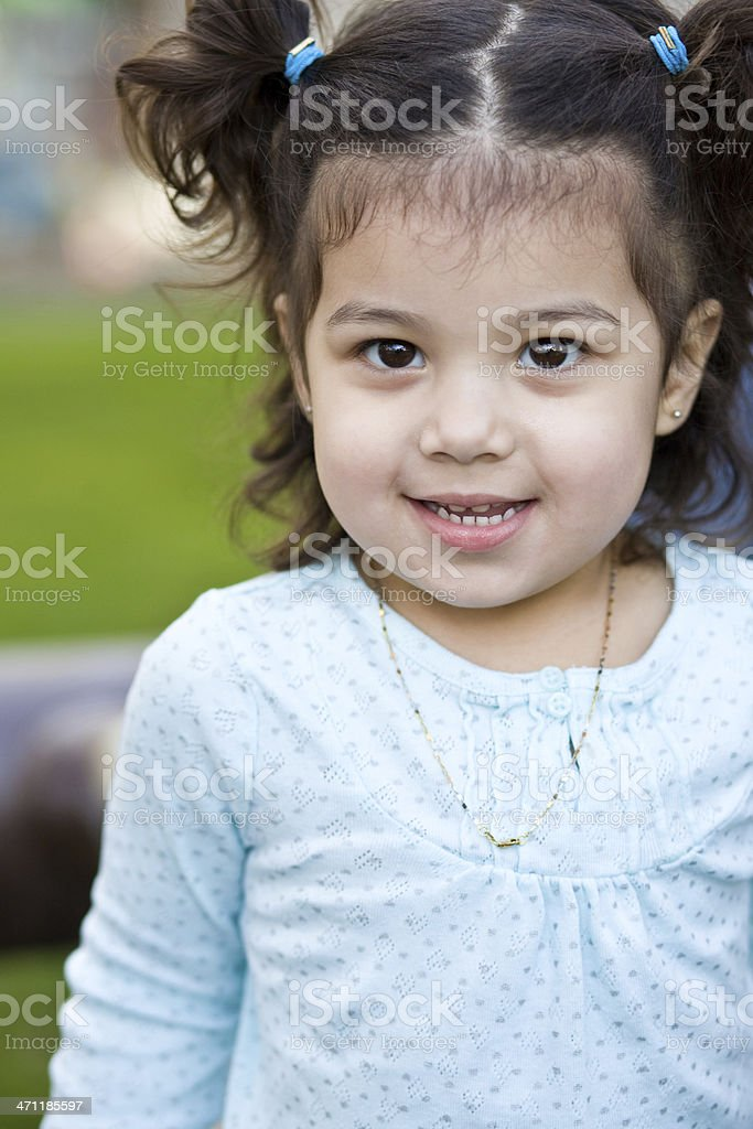 young hispanic girl with pigtails smiling in a park royalty-free stock photo