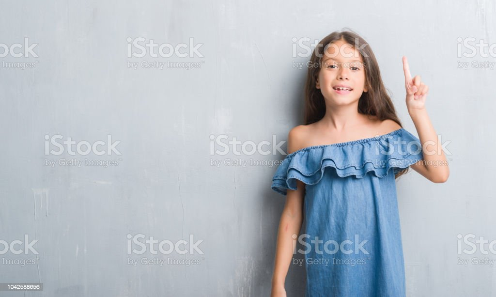 Young hispanic kid over grunge grey wall showing and pointing up with finger number one while smiling confident and happy. stock photo