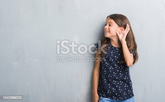 Young hispanic kid over grunge grey wall smiling with hand over ear listening an hearing to rumor or gossip. Deafness concept.