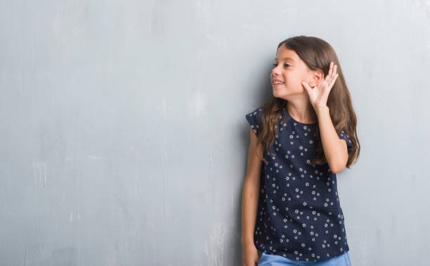 unga spansktalande barn över grunge grå vägg ler med handen över örat lyssnar en hearing rykten eller skvaller. dövhet-konceptet. - listen bildbanksfoton och bilder