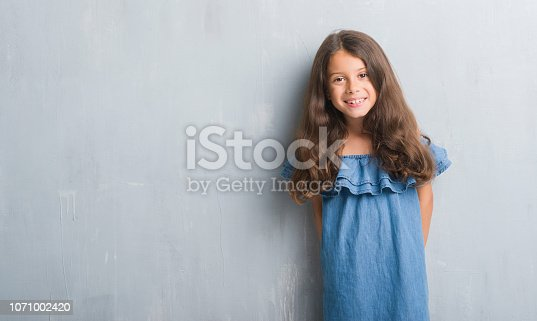 Young hispanic kid over grunge grey wall with a happy and cool smile on face. Lucky person.