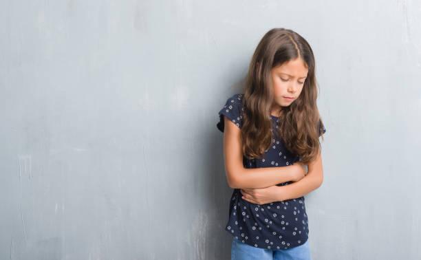 unga spansktalande barn över grunge grå vägg med handen på magen eftersom matsmältningsbesvär, smärtsam sjukdom sjukdomskänsla. värka koncept. - matsmältningsbesvär bildbanksfoton och bilder