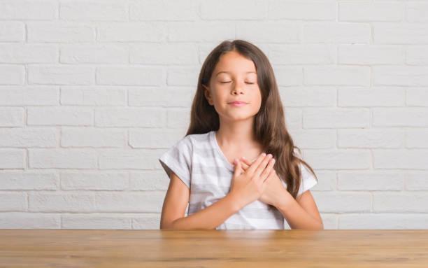 hispanische zicklein auf dem tisch zu hause lächelnd mit händen auf brust mit geschlossenen augen und dankbar geste auf gesicht. gesundheitskonzept. - die wahrheit tut weh stock-fotos und bilder