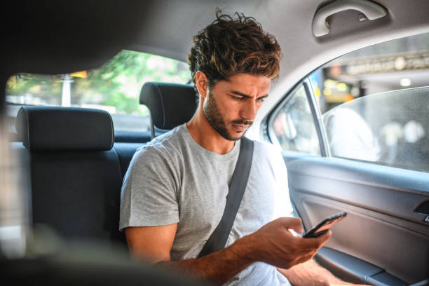 Young Hispanic Male Checking Smart Phone in Backseat of Car stock photo