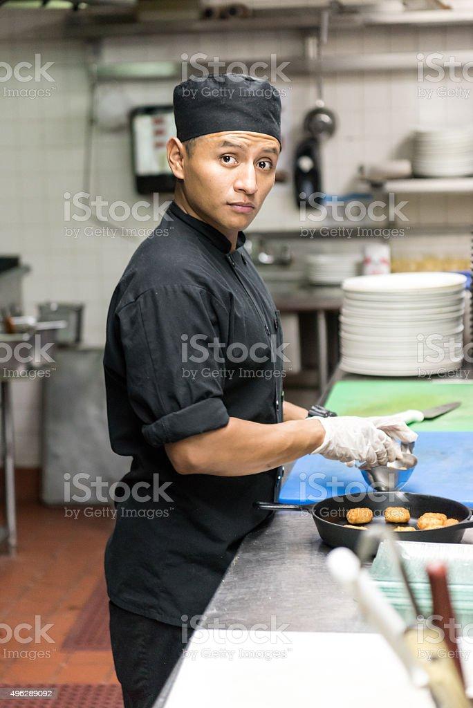 Young hispanic male kitchen worker working stock photo