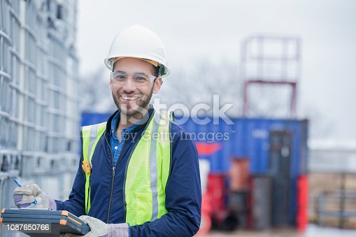 Young adult Hispanic man is chemical engineer, checking inventory of chemical shipment at oil and gas industry job site. Pipeline pipes and other equipment are in background. Man is wearing safety gear and using a clipboard.