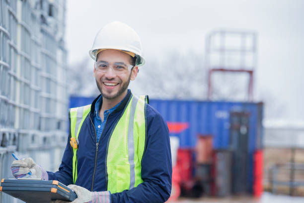 Young Hispanic man is chemical engineer working outdoors at oil and gas pipeline job site. Young adult Hispanic man is chemical engineer, checking inventory of chemical shipment at oil and gas industry job site. Pipeline pipes and other equipment are in background. Man is wearing safety gear and using a clipboard. chemical plant stock pictures, royalty-free photos & images