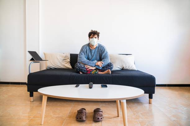 Young hispanic man sits on the couch while protecting against COVID-19 coronavirus due to it's virulency and impact on media and society Young hispanic man sits on the couch while protecting against COVID-19 coronavirus due to it's virulency and impact on media and society quarantine stock pictures, royalty-free photos & images