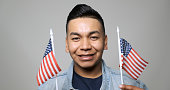 Young hispanic man waving small US flags on gray background