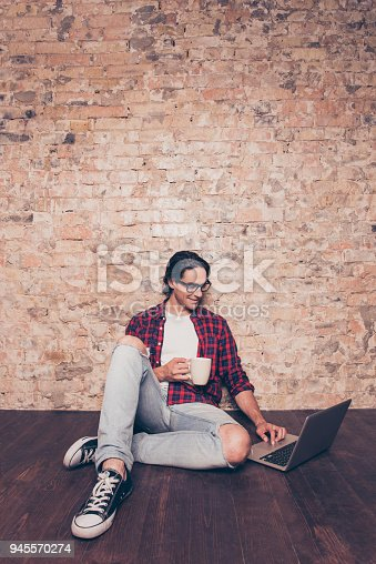 947303582 istock photo Young hispanic man with cup of coffee typing on laptop 945570274
