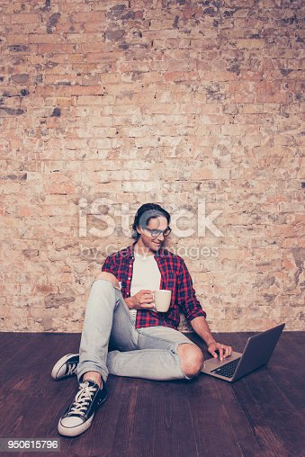 947303582 istock photo Young hispanic man with cup of coffee typing on laptop 950615796
