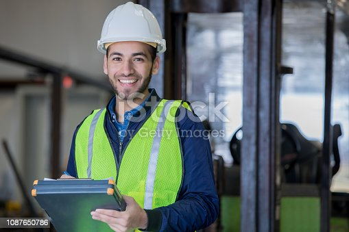 Young adult Hispanic man is smiling and looking at the camera while working in warehouse as forklift operator. Man is using a clipboard and wearing a hard hat and safety gear while standing in front of forklift.
