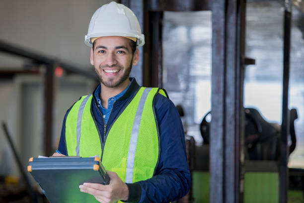 Young Hispanic man working as forklift operator in large warehouse smiles while wearing safety gear Young adult Hispanic man is smiling and looking at the camera while working in warehouse as forklift operator. Man is using a clipboard and wearing a hard hat and safety gear while standing in front of forklift. driver occupation stock pictures, royalty-free photos & images