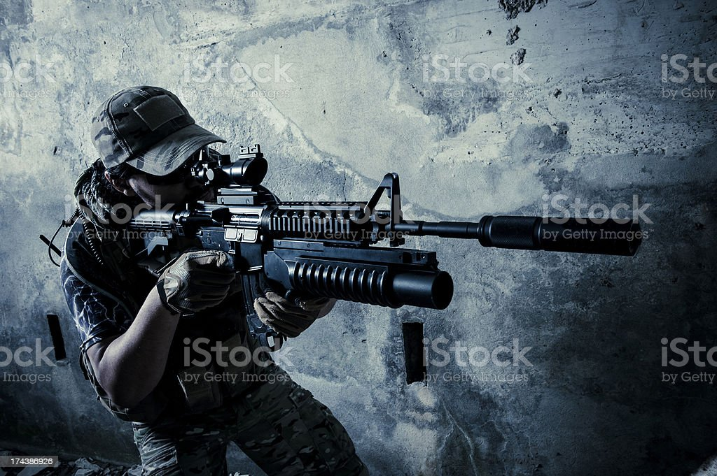 Young Hispanic Modern Army Soldier Shooting with Rifle by Night stock photo