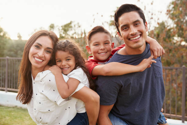 Young Hispanic parents piggyback their children in the park, smiling to camera, focus on foreground stock photo