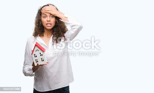 istock Young hispanic real state agent woman holding small house stressed with hand on head, shocked with shame and surprise face, angry and frustrated. Fear and upset for mistake. 1044207090