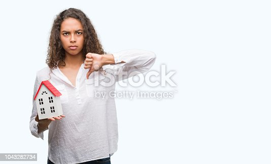 Young hispanic real state agent woman holding small house with angry face, negative sign showing dislike with thumbs down, rejection concept