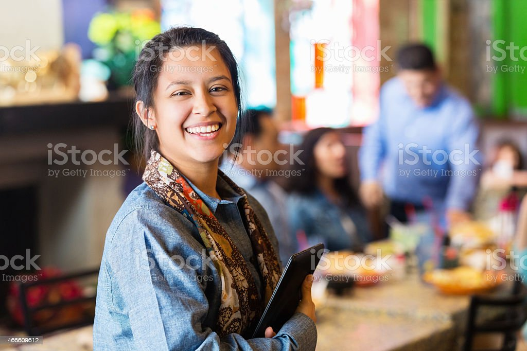 Young Hispanic restaurant manager standing with digital tablet stock photo
