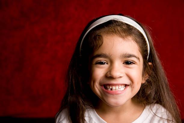 Young Hispanic School Girl with Toothy Smile stock photo