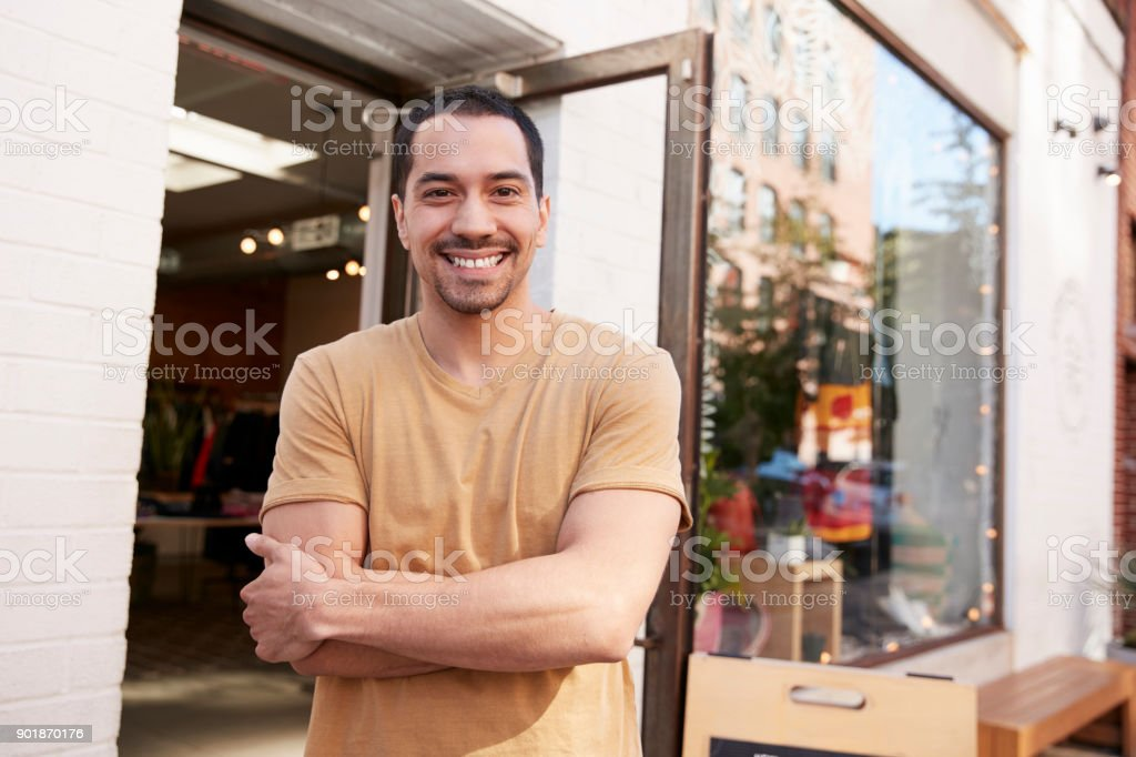 Young Hispanic shop owner smiling to camera outside his shop royalty-free stock photo