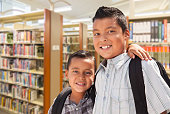 Young Hispanic Student Brothers In Library Wearing Backpacks