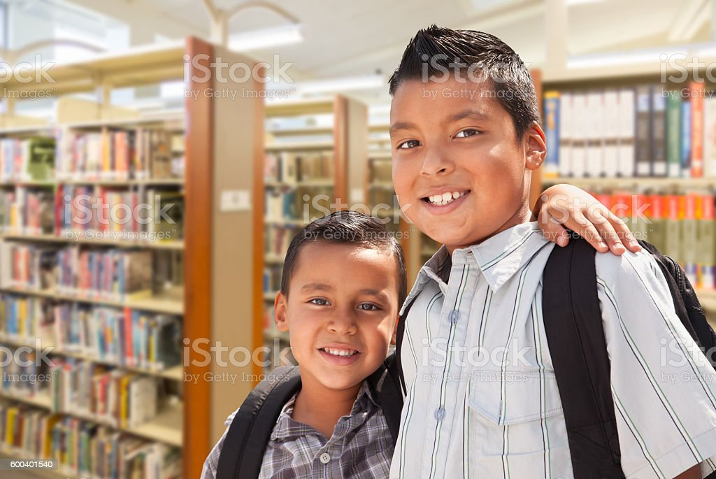 Young Hispanic Student Brothers In Library Wearing Backpacks stock photo